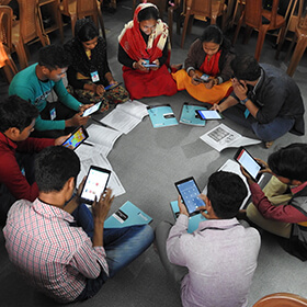 Students, who have always learned in traditional lecture-oriented classrooms, learn English in peer groups using tablets and smart phones.