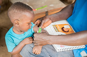 Child being assessed by CHAs in Liberia
